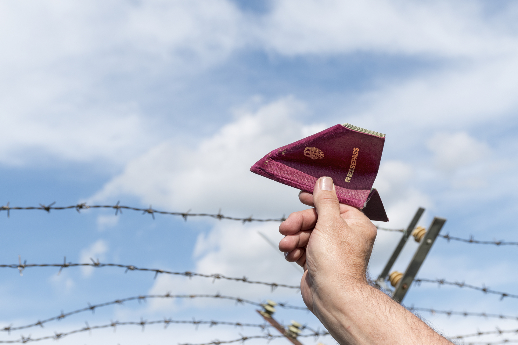 man's hand holding a German passport as a paper airplane over a barbed wire fence against the blue sky, copy space